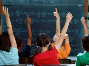 elementary_school_kids_raise_hand_in_class_4x3